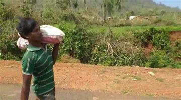Khabar Odisha:carrying-the-body-of-his-minor-daughter-killed-in-CycloneTitli-on-his-shoulders-at-Atankpur-in-Raygad-block